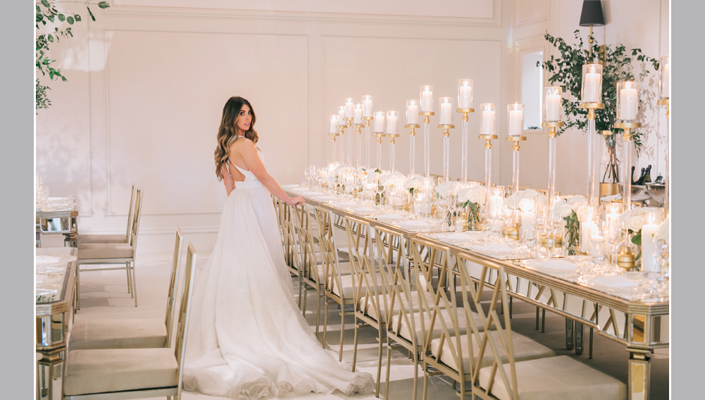 bride at her reception, long mirror table with white flowers and lots of candlelight, wedding decor