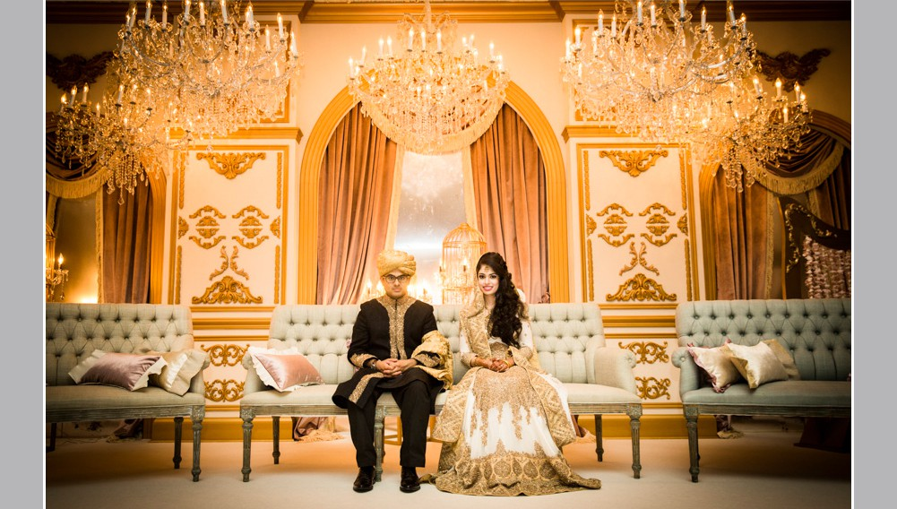 wedding couple in traditional Indian attire seated on a sofa , wedding stage decor