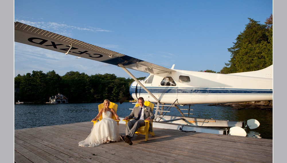 wedding couple sitting on a dock in Muskoka with a water plane behind them , wedding day photo