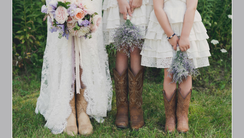 country wedding, bride standing with flower girls, cowboy boots , holding purple and pink flowers