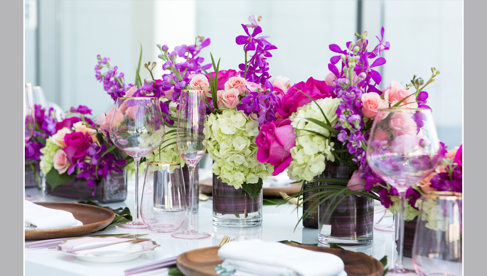 bright coloured flowers , place setting with blush coloured glasses and blush and gold cutlery